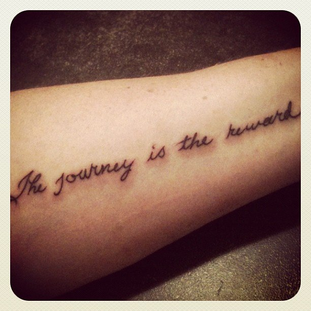 photo of tattoo that says the journey is the reward